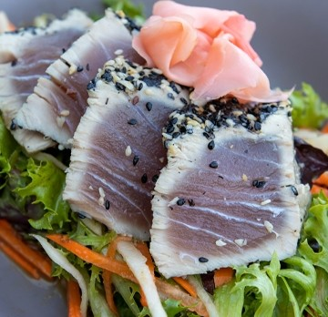 Thinly sliced seasoned fish on vegetables and with ginger