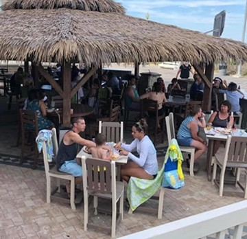 Patrons sitting outside at tables under the tiki hut